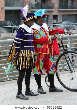 AALST, BELGIUM, NOVEMBER 5 2016: Two colourfully dressed 'Zwarte Piets' (Black Petes) during the arrival of Saint Martin at the Werf Quay in Aalst. Piet is the traditional helper of the Saint.