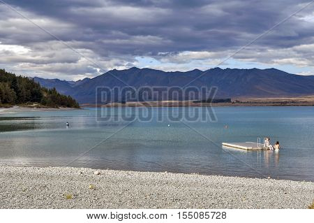 Tekapo, New Zealand - February 2016: People Swimming At At Lake Tekapo, South Island Of New Zealand