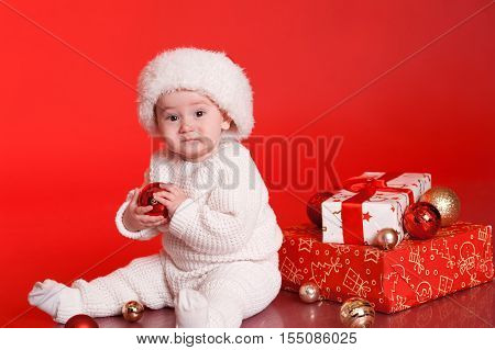 Cute baby boy 1 year old playing with christmas decorations, presents over red. Little child wearing trendy knitted clothes, santa hat in room.