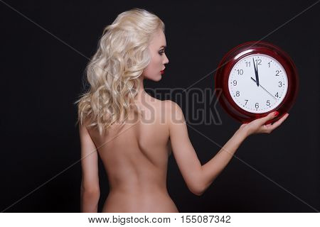 Beautiful naked woman holding in hands big red clock.