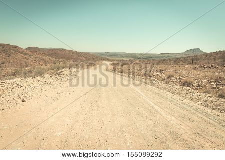 Gravel winding road crossing the Namib desert in the majestic Namib Naukluft National Park best travel destination in Namibia Africa. Toned image vintage old retro filter.