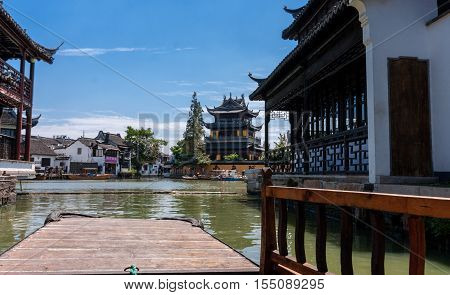 ZHUJIAJIAO CHINA - AUGUST 30 2016: Tourists see the sights of ancient water town with a history of more than 1700 years near Yuanjin Buddhist temple in Zhujiajiao China on August 30 2016.