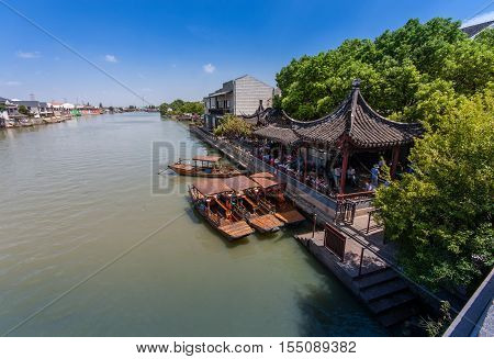 ZHUJIAJIAO CHINA - AUGUST 30 2016: Chinese gondolas waits Tourists on canal of ancient water town with a history of more than 1700 years in Zhujiajiao China on August 30 2016.