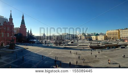 MOSCOW RUSSIA - FEBRUARY 18 2016: Unidentified people walk on Manezhnaya Square near Historical museum and Central Exhibition Hall Manege in Moscow Russia on February 18 2016.