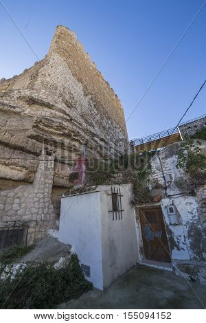 Alcala del Jucar Spain - October 29 2016: typical house of La Mancha placed in the skirts of the castle on top of limestone mountain is situated Castle of the 12TH century Almohad origin take in Alcala del Jucar Albacete province Spain