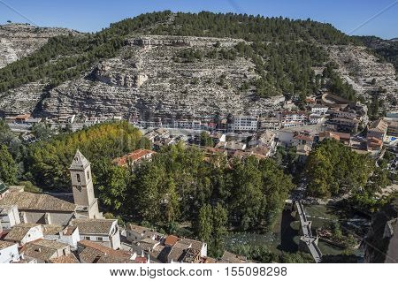 Alcala del Jucar Spain - October 29 2016: To the left the church of San Andres and to the right the roman bridge panoramic view from the castle during autumn take in Alcala of the Jucar Albacete province Spain