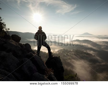 Hiker stand at heather bush on the corner of empire bellow pine tree. Man is watching over the misty and foggy morning valley to Sun poster