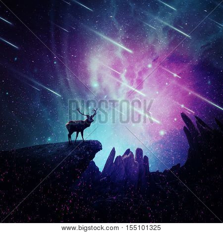 Majestic deer with long stand on the peak of a rocky hill below a wonderful night sky with falling stars and sparkles. Mystic wild scene screen saver.