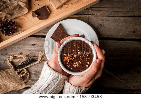 Girl drinks hot chocolate mug, with christmas present on rustic table with blanket or plaid from above, cozy and tasty breakfast or snack. Hands in picture, top view