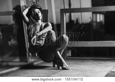 Fashion beautiful female model posing outdoor in fashion dress. Attractive blonde woman wearing long red trousers and sitting on roof against glass wall at sunset. Black and white photo.