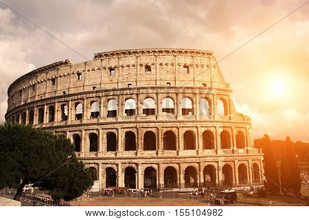 A beautiful sunset lights the side of ancient amphitheater Colosseum, Rome, Italy. Photo toned in orange color