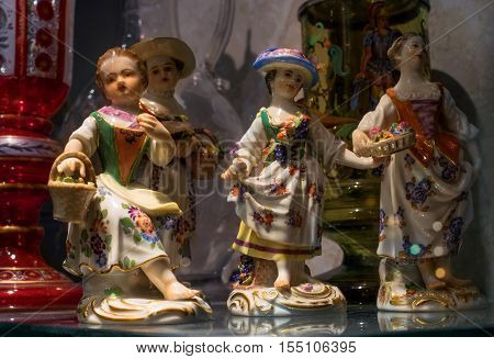 Munich, Germany - October 12, 2016: Showcase antique shop. In the showcase presented porcelain figurines. Four lovely girls with flowers and fruits.