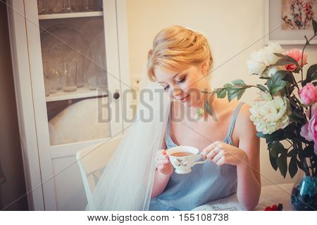 Beautiful young bride with wedding makeup and hairstyle in bedroom. Morning of the bride. Posing on the bed on the wedding morning. Beautiful young woman in negligee in the morning drinking tea.