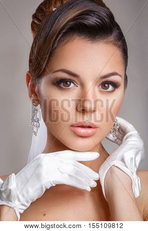 Beautiful bride with fashion wedding hairstyle - on white background. Closeup portrait of young gorgeous bride in satin gloves. Wedding. Studio shot. Beautiful bride portrait with veil