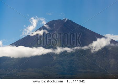 Hakone Japan - September 27 2016: The summit of mount Fuji against blue sky clearly visible from the Fujikya area. A few white clouds create a band halfway up the mountain. Forested foreground.