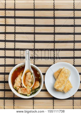 Bowl of delicious traditional japanese miso soup with wakame seaweed and white ceramic spoon in it plate with sliced fried tofu standing on striped bamboo mat.