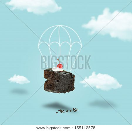 Isolated Chocolate cherry cake with parachute on blue sky background. Chocolate pie. Flying brownie with cream. Chocolate cherry cake with parachute without text.