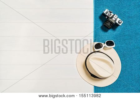 Top view of beach summer accessories with copy space. Lay flat holiday fashion background on white wooden table or floor. Horizontal frame for spa or wellness concept.