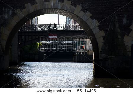 Hamburg City amorous couple sitting together at alster River under a bridge
