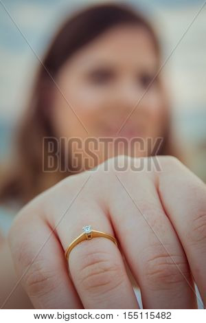 Happy woman shows off her new engagement ring on her finger. Closeup blur background.