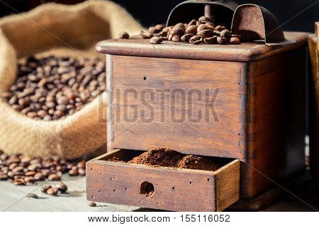 Ground coffee in vintage grider on old wooden table