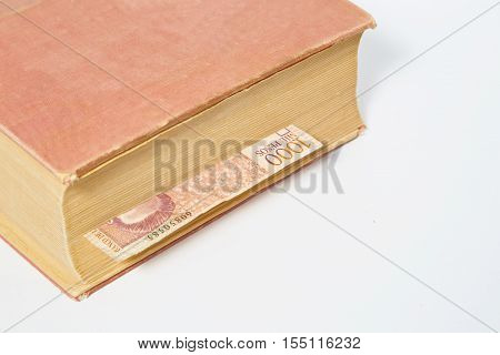 Thousand Colombian pesos in book isolated on white