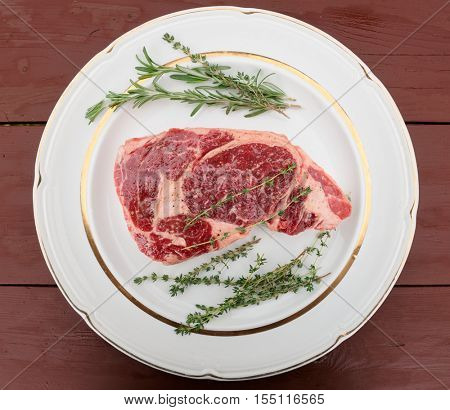 Raw rib-eye steak withe herbs on plate, old wooden table