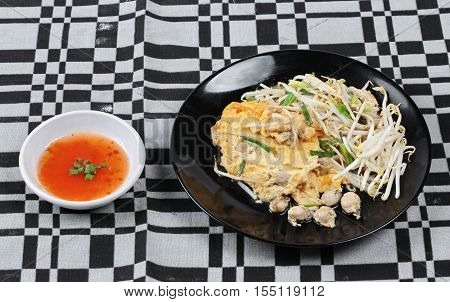 Thai food,Fried egg and oyster with bean sprouts and shallot as Hoi Tod Khai in Thai served with chili sauce.