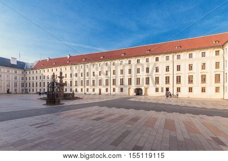 The Second Courtyard of Prague Castle. Direction south-west. In the middle of courtyard there is Kohl's fountain and the well a bit on the left. The president flag on the roof. Western gate and courtyard surrounded by representative residential and galler