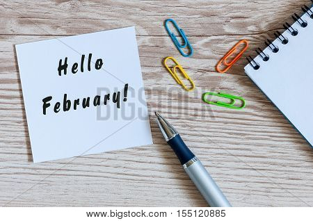 hello February on peace of paper near office suplies at workplace background.