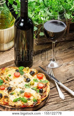 Freshly baked pizza served with wine on old wooden table