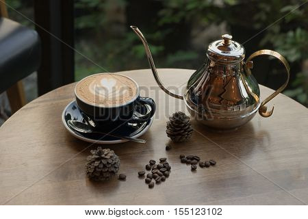hot fresh coffee in white glass with tree shape of heart foam shinny coffee pot on wooden table at sunset at coffee time / hot fresh coffee