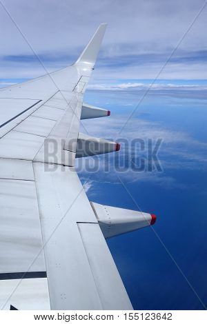 Wing of an airplane flying above the clouds on blue sky background