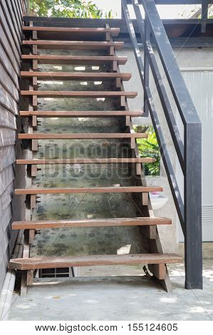 Exterior brown wooden staircase with iron banister stock photo