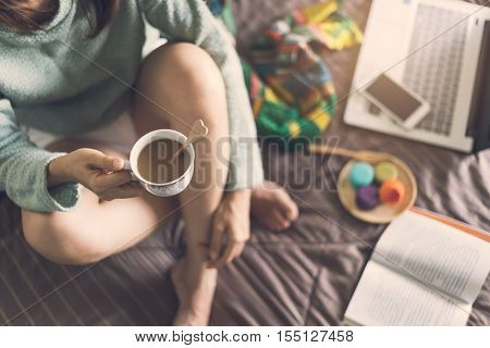 Young woman relaxing at cozy home atmosphere on the bed with cup of coffee and macaroon.