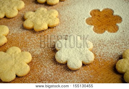 Homemade shortbread flower shape cookies with sugar powder on wooden table, top view, toned