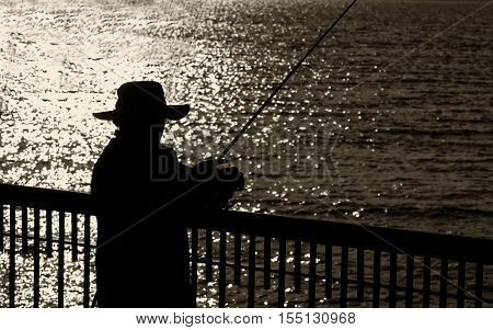 Silhouette image of a fisherman in early morning