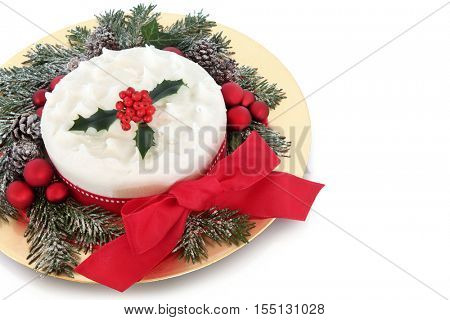 Traditional christmas cake with red bauble decorations, bow, holly and snow covered winter greenery on a gold plate over white  background with copy space.