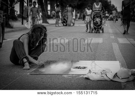 Pescara Italy - August 13 2016: Pescara Italy. Woman artist drawing on the street. Black and white photography
