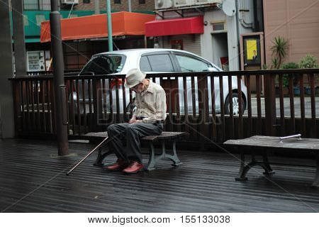 Hyogo,Japan-June 26 , Old man sit motionless on  bench with discretionary in happiness  near JR-Hyogo station,Hyogo,Japan on June 26 ,2016