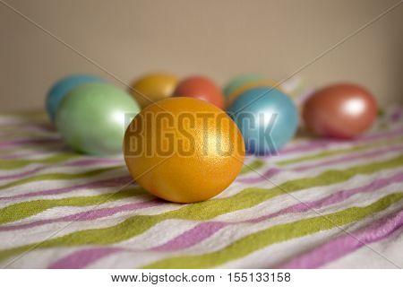 The Easter eggs painted by nacreous paint on a multi-colored striped napkin
