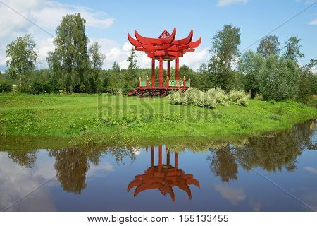 ANDRIANOVO, RUSSIA - JULY 31, 2016: A summer landscape with a red japanese arbor. Estate Maryino Leningrad region. The historical landmark