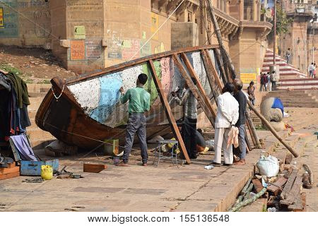 VARANASI, UTTAR PRADESH, INDIA - FEBRUARY 17, 2016 - Unidentified indian people repairing a wooden boat on the ghats
