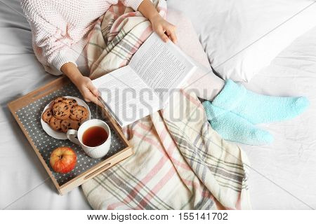 Girl with food reading book on bed