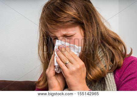 Sick Woman Having Flu And Sneezing Into Handkerchief