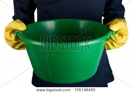 Human in dark-blue shirt and yellow rubber gloves holds small green washbowl. Isolated on white