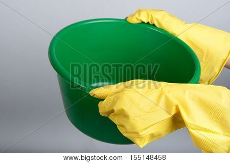 Human hands in yellow rubber gloves hold green washbowl