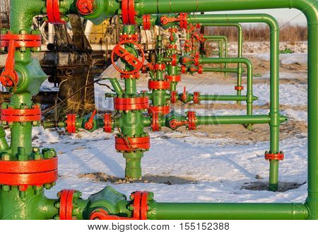 Group of wellheads. Oilfield during winter time. Oil and gas concept.