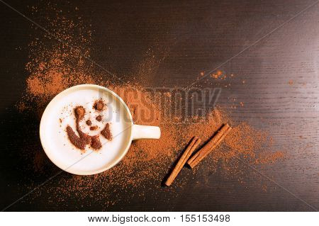 Cup of coffee with panda pattern of cinnamonon dark background