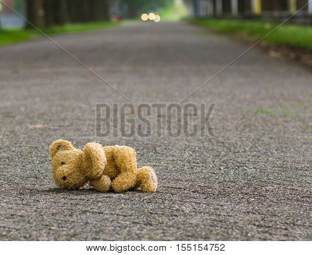 Teddy bear lies alone on the road